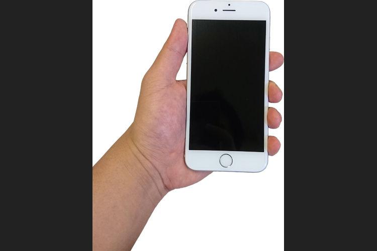 白いスマートフォンを握っている